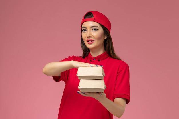 Vooraanzicht jonge vrouwelijke koerier in rood uniform en cape met kleine bezorgvoedselpakketten op haar handen op de roze muur