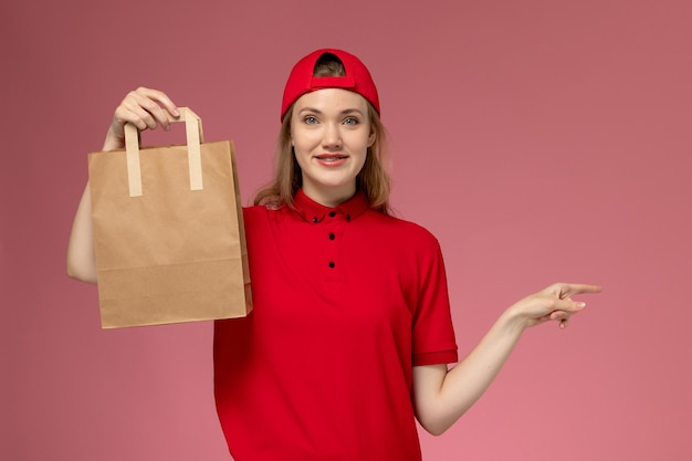 Vooraanzicht jonge vrouwelijke koerier in rood uniform en cape met levering voedselpakket met glimlach op roze muur