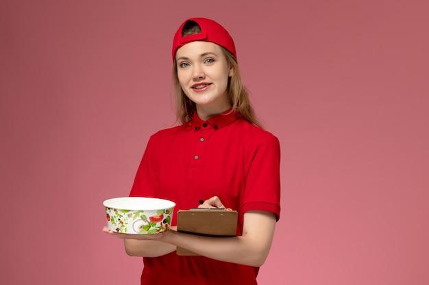 Vooraanzicht jonge vrouwelijke koerier in rood uniform en cape met leveringskom en blocnote schrijven van notities op de roze muur
