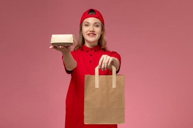 Vooraanzicht jonge vrouwelijke koerier in rood uniform en cape met voedselpakketten voor levering op de roze muur