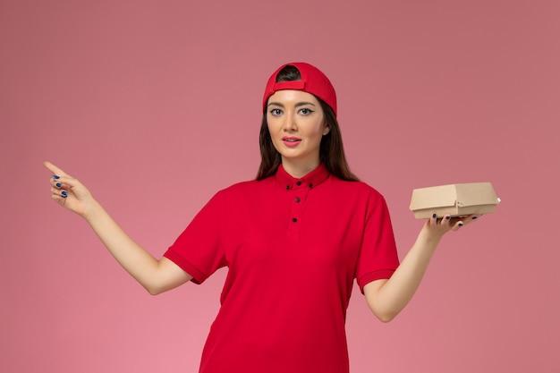 Vooraanzicht jonge vrouwelijke koerier in rood uniform en cape met weinig voedselpakket voor bezorging op haar handen op de roze muur