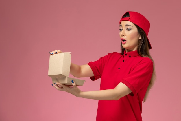 Vooraanzicht jonge vrouwelijke koerier in rood uniform en cape met weinig voedselpakket voor bezorging op haar handen op lichtroze muur
