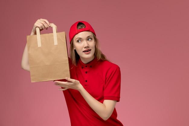 Vooraanzicht jonge vrouwelijke koerier in rood uniform en kaap die voedselpakket voor levering op de roze muur houden