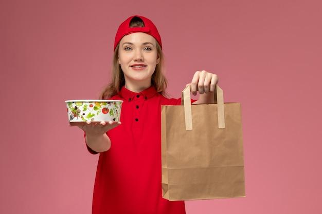 Vooraanzicht jonge vrouwelijke koerier in rood uniform het voedselpakket en de kom van de holdingslevering op de lichtroze muur