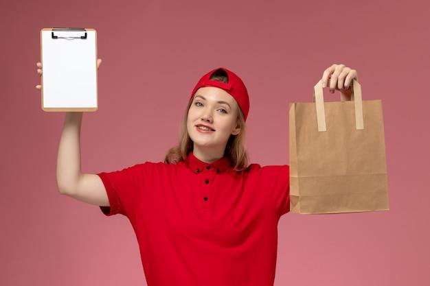 Vooraanzicht jonge vrouwelijke koerier in rood uniform het voedselpakket van de holdingslevering en blocnote glimlachen op lichtroze muur