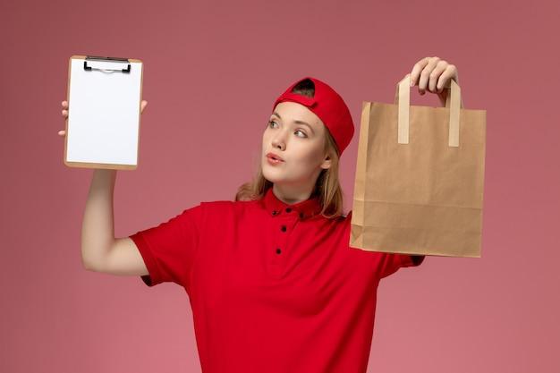 Vooraanzicht jonge vrouwelijke koerier in rood uniform het voedselpakket van de holdingslevering en blocnote op de lichtroze muur
