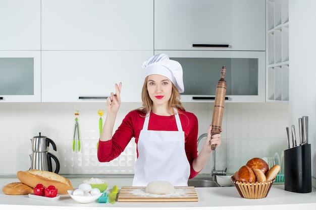 Vooraanzicht jonge vrouwelijke kok die deegroller vasthoudt en geluk tekent in de keuken