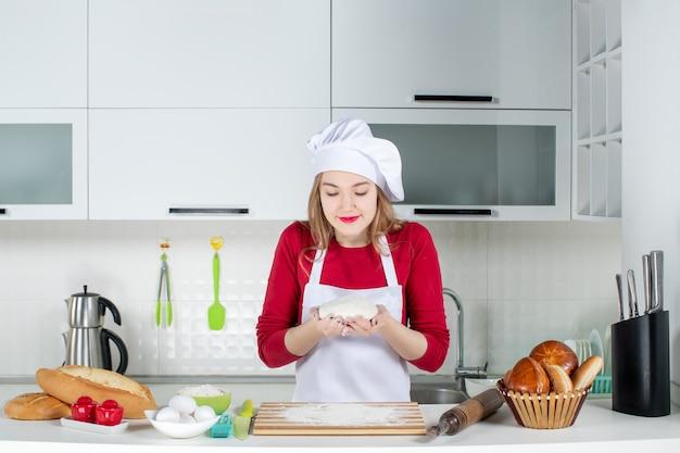Vooraanzicht jonge vrouwelijke kok in koksmuts en schort die deeg met beide handen in de keuken vasthouden