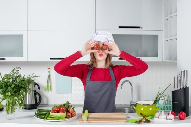 Vooraanzicht jonge vrouwelijke kok in schort die tomaten voor haar ogen houdt