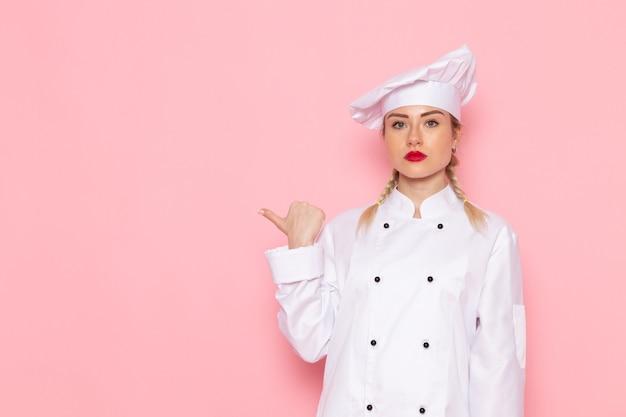 Vooraanzicht jonge vrouwelijke kok in wit kokkostuum die eenvoudig op de roze ruimtekok stellen