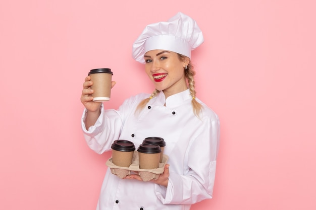 Vooraanzicht jonge vrouwelijke kok in wit kokkostuum die plastic koffiekopjes op de roze foto van de ruimtekok houden