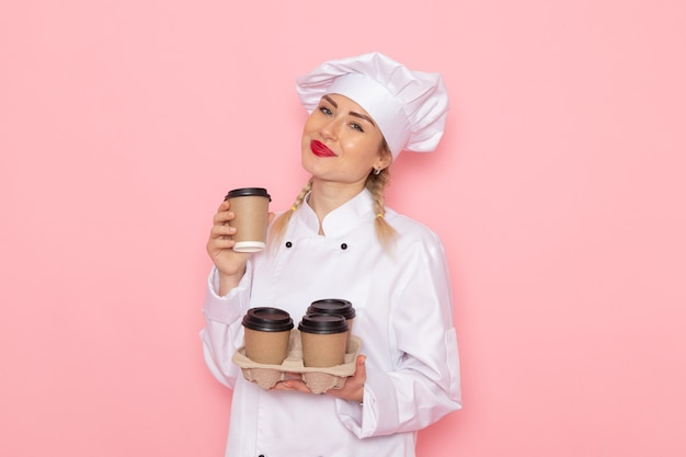 Vooraanzicht jonge vrouwelijke kok in wit kokkostuum die plastic koffiekopjes op de roze foto van de ruimtekookkeuken houden