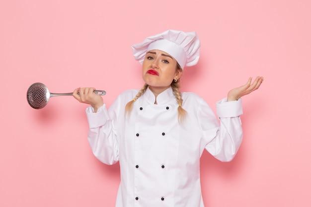 Vooraanzicht jonge vrouwelijke kok in wit kokkostuum die zilveren lepel met verwarde uitdrukking op de roze ruimtekok houden