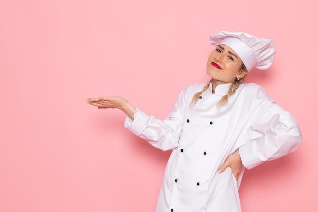 Vooraanzicht jonge vrouwelijke kok in witte kok pak poseren helemaal op de roze ruimte kok keuken werk foto