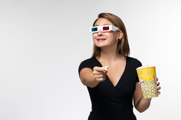 Vooraanzicht jonge vrouwelijke popcorn houden en eten in d zonnebril kijken naar film op wit oppervlak