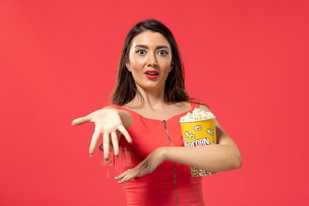 Vooraanzicht jonge vrouwelijke popcorn houden op het rode oppervlak