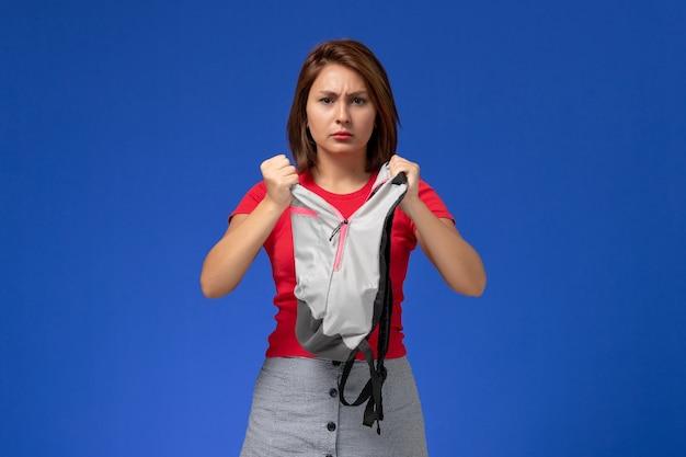 Vooraanzicht jonge vrouwelijke student die in rood overhemd grijze rugzak op lichtblauwe achtergrond houdt.