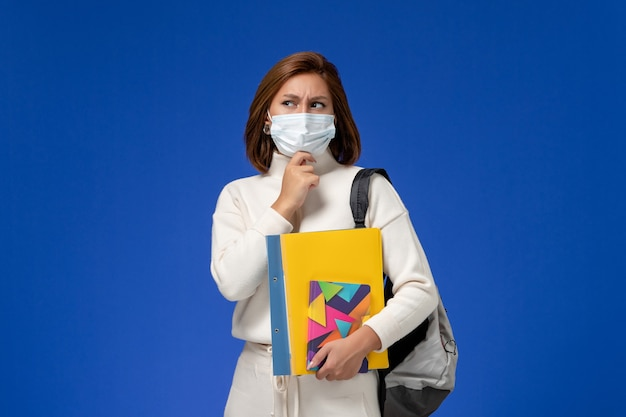Vooraanzicht jonge vrouwelijke student die in witte jersey masker met zak en voorbeeldenboeken draagt die aan de blauwe muur denken