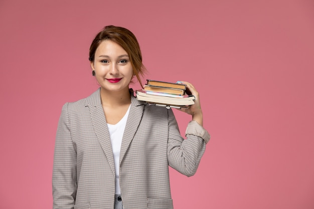 Vooraanzicht jonge vrouwelijke student in grijze jas glimlachend bedrijf boeken op roze achtergrond les universiteit college studieboek
