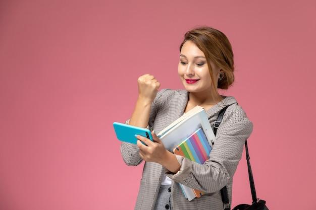 Vooraanzicht jonge vrouwelijke student in grijze jas met voorbeeldenboeken en met behulp van een telefoon met een glimlach op de roze achtergrondlessen universiteit college studie