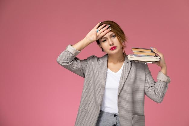 Vooraanzicht jonge vrouwelijke student in grijze jas met voorbeeldenboeken moe van roze achtergrondlessen universiteit college studie