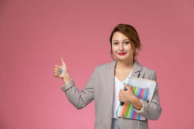 Vooraanzicht jonge vrouwelijke student in grijze jas met voorbeeldenboeken op roze achtergrondlessen hogeschool