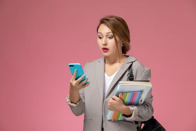 Vooraanzicht jonge vrouwelijke student in grijze jas poseren bedrijf boeken met behulp van een telefoon op de roze achtergrond lessen hogeschool studie