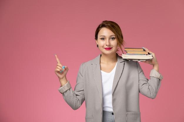 Vooraanzicht jonge vrouwelijke student in grijze jas poseren en houden boeken met glimlach op de roze achtergrond lessen universiteit college studie