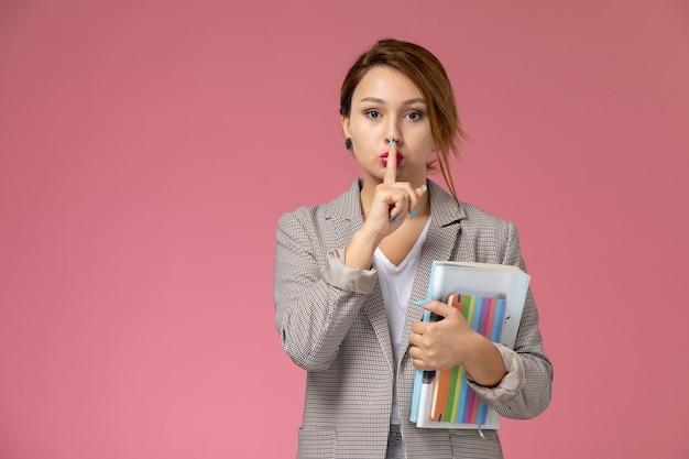 Vooraanzicht jonge vrouwelijke student in grijze jas poseren en houden voorbeeldenboeken op roze achtergrond lessen universiteit college studie