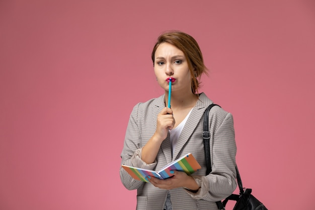 Vooraanzicht jonge vrouwelijke student in het grijze voorbeeldenboek van de vachtholding die op de roze studie van de achtergrondlessen hogeschool denken