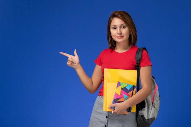 Vooraanzicht jonge vrouwelijke student in rood overhemd die de dossiers en voorbeeldenboek van de rugzakholding op de blauwe achtergrond dragen.