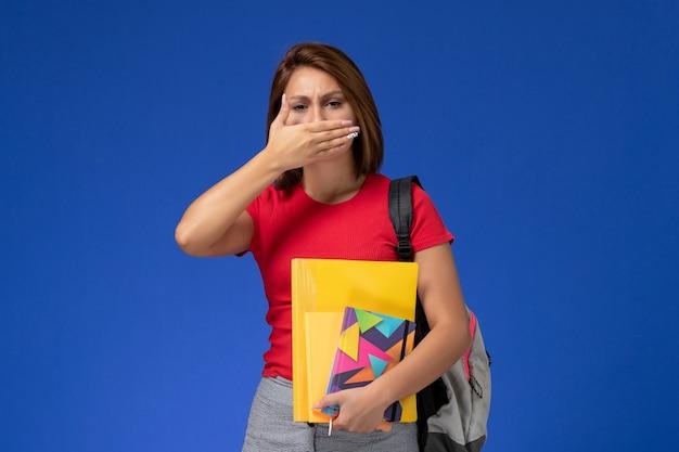 Vooraanzicht jonge vrouwelijke student in rood overhemd die de dossiers van de rugzakholding en voorbeeldenboek dragen die haar mond op blauwe achtergrond sluiten.