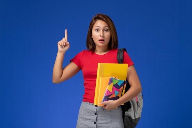 Vooraanzicht jonge vrouwelijke student in rood overhemd die de dossiers van de rugzakholding en voorbeeldenboek dragen die haar vinger op blauw bureau opheffen.