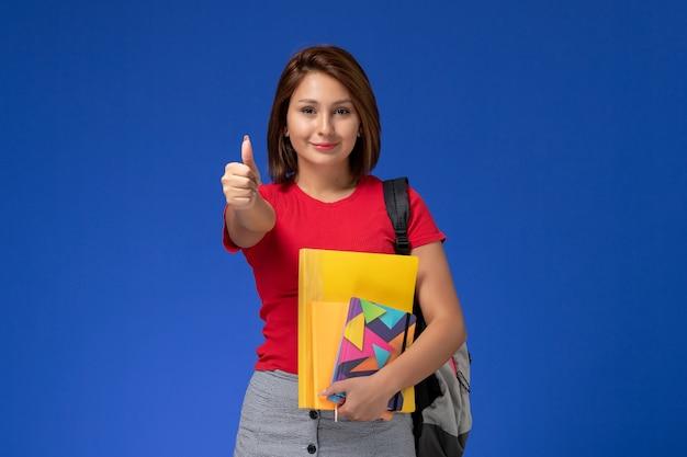 Vooraanzicht jonge vrouwelijke student in rood overhemd die de dossiers van de rugzakholding en voorbeeldenboek dragen die op blauwe achtergrond glimlachen.