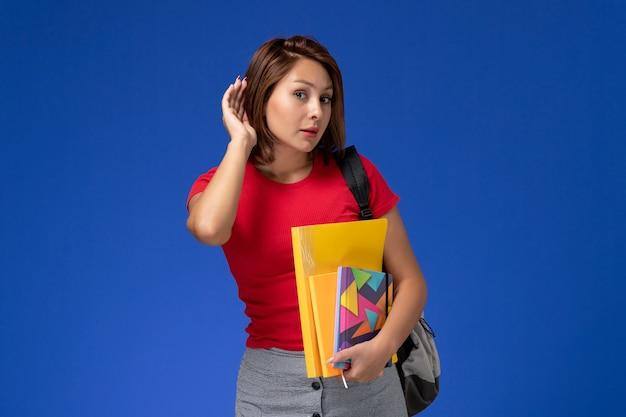Vooraanzicht jonge vrouwelijke student in rood overhemd die de dossiers van de rugzakholding en voorbeeldenboek dragen die op blauwe achtergrond proberen te horen.
