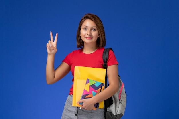 Vooraanzicht jonge vrouwelijke student in rood overhemd die de dossiers van de rugzakholding en voorbeeldenboek dragen die op blauwe achtergrond stellen.