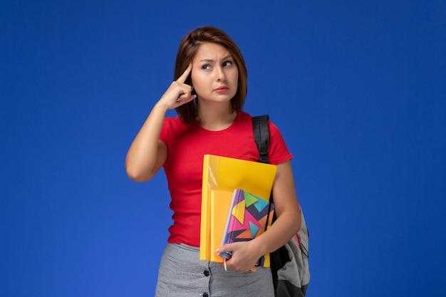 Vooraanzicht jonge vrouwelijke student in rood overhemd die de dossiers van de rugzakholding en voorbeeldenboek dragen die op de blauwe achtergrond denken.
