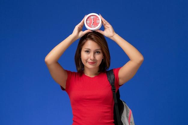 Vooraanzicht jonge vrouwelijke student in rood overhemd die de klokken van de rugzakholding dragen die op lichtblauwe achtergrond glimlachen.