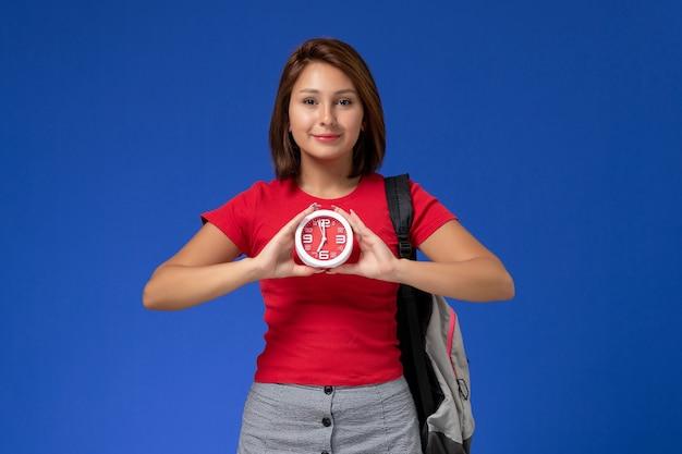 Vooraanzicht jonge vrouwelijke student in rood overhemd die de klokken van de rugzakholding met glimlach op lichtblauwe achtergrond dragen.