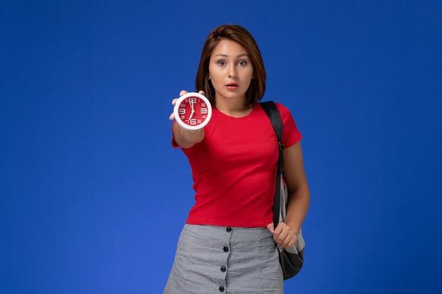 Vooraanzicht jonge vrouwelijke student in rood overhemd die de klokken van de rugzakholding op de lichtblauwe achtergrond dragen.