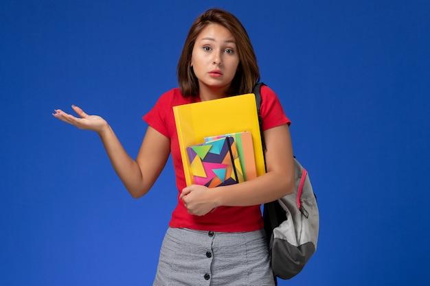 Vooraanzicht jonge vrouwelijke student in rood overhemd die de voorbeeldenboek en dossiers van de rugzakholding op de lichtblauwe achtergrond dragen.