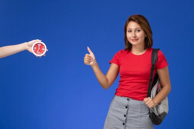 Vooraanzicht jonge vrouwelijke student in rood overhemd die rugzak draagt die als teken op lichtblauwe achtergrond toont.