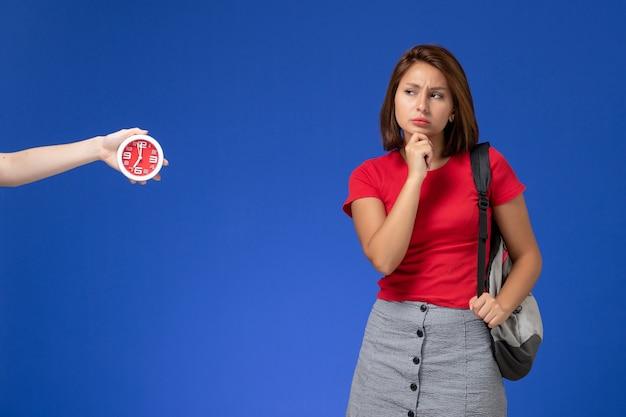 Vooraanzicht jonge vrouwelijke student in rood overhemd die rugzak draagt die op lichtblauwe achtergrond denken.