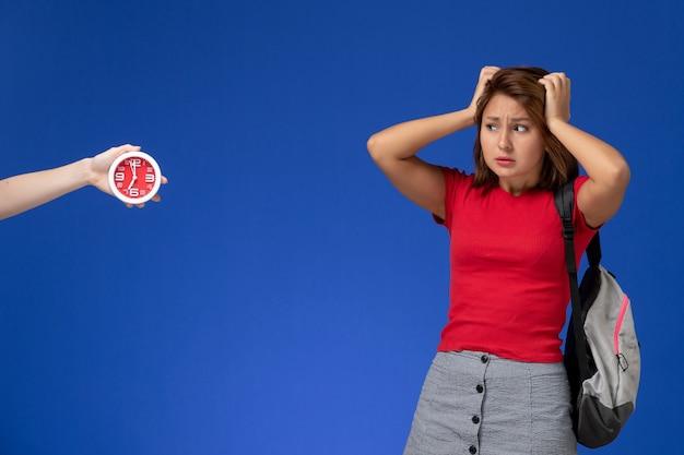 Vooraanzicht jonge vrouwelijke student in rood overhemd die rugzak op de lichtblauwe achtergrond draagt.