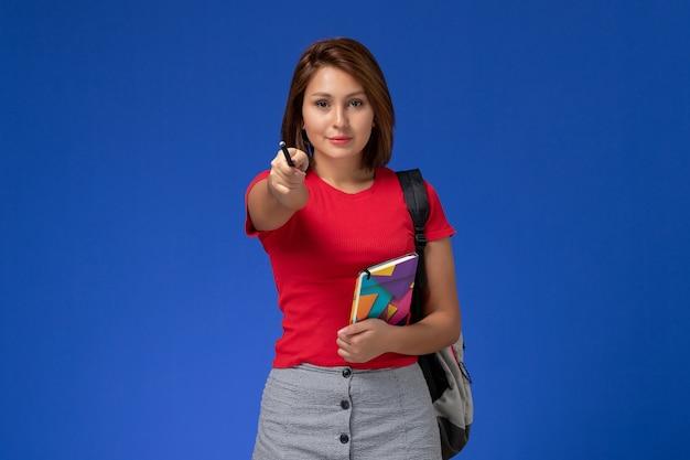 Vooraanzicht jonge vrouwelijke student in rood overhemd die voorbeeldenboek van de rugzakholding met pen op lichtblauwe achtergrond dragen.