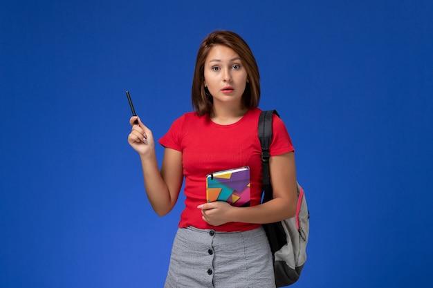 Vooraanzicht jonge vrouwelijke student in rood overhemd die voorbeeldenboek van de rugzakholding op de blauwe achtergrond dragen.