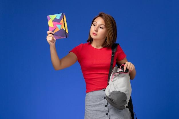 Vooraanzicht jonge vrouwelijke student in rood overhemd die voorbeeldenboek van de rugzakholding op lichtblauwe achtergrond dragen.