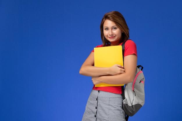 Vooraanzicht jonge vrouwelijke student in rood overhemd met rugzak die gele dossiers houdt en op lichtblauwe achtergrond glimlacht.