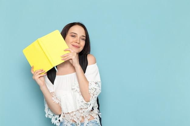 Vooraanzicht jonge vrouwelijke student in wit overhemd, spijkerbroek en zwarte tas met gele voorbeeldenboek op de blauwe ruimte vrouwelijke studentenuniversiteit