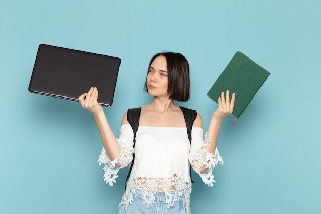 Vooraanzicht jonge vrouwelijke student in wit overhemd, spijkerbroek en zwarte tas met voorbeeldenboek en laptop op de blauwe ruimte vrouwelijke student universitaire school